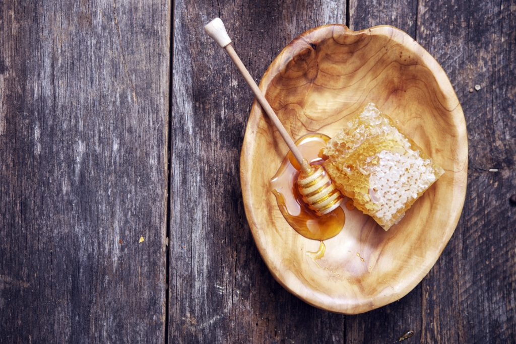 Honeycomb and Dipper in Wooden Bowl on Wooden Table.