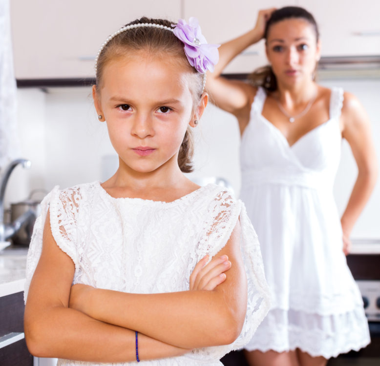 Portrait of quarrelling young woman and little girl indoors