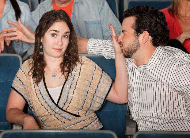 Irritated girlfriend stops misbehaving boyfriend in theater