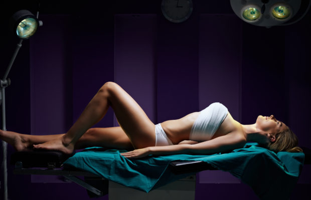 woman in dark surgery room lieing on surgical table under light for bueauty surgery