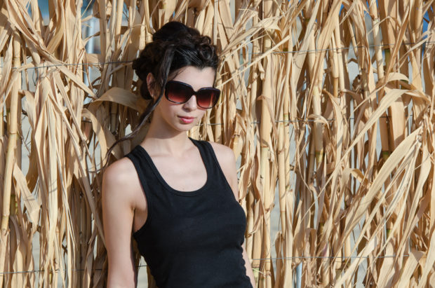 Sweet lady with slim body wear sleeveless and sunglasses, leaning against reeds wall