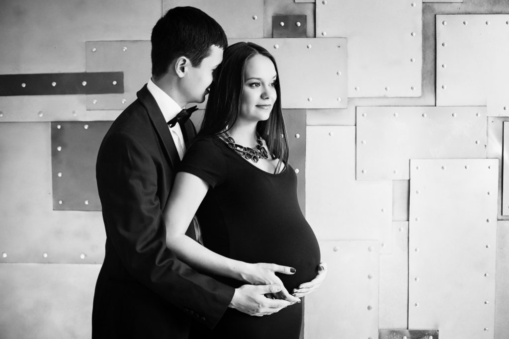 Young elegance pregnant family. Beautiful stylish couple. Black and white.