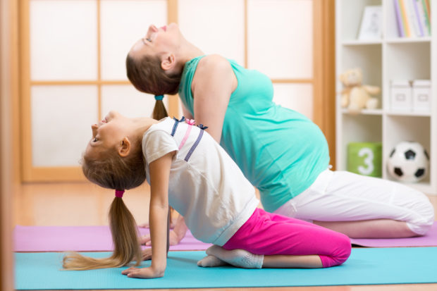 Pregnant woman with elder child daughter doing gym fitness exercise