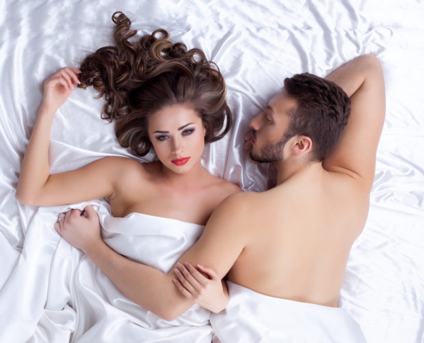 Couple of handsome young lovers posing lying on silk sheets