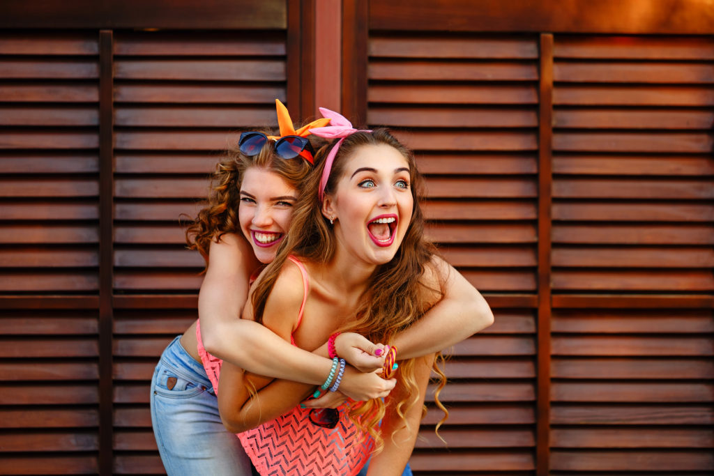 Best friends are dressed in the style of pin-up. Girls laugh. Piggyback. The concept of true friendship.