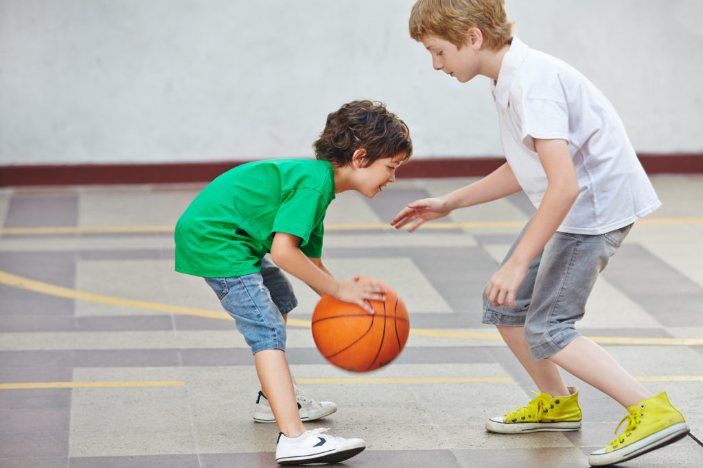 Two boys playing basketball together in the schoolyard of a school
