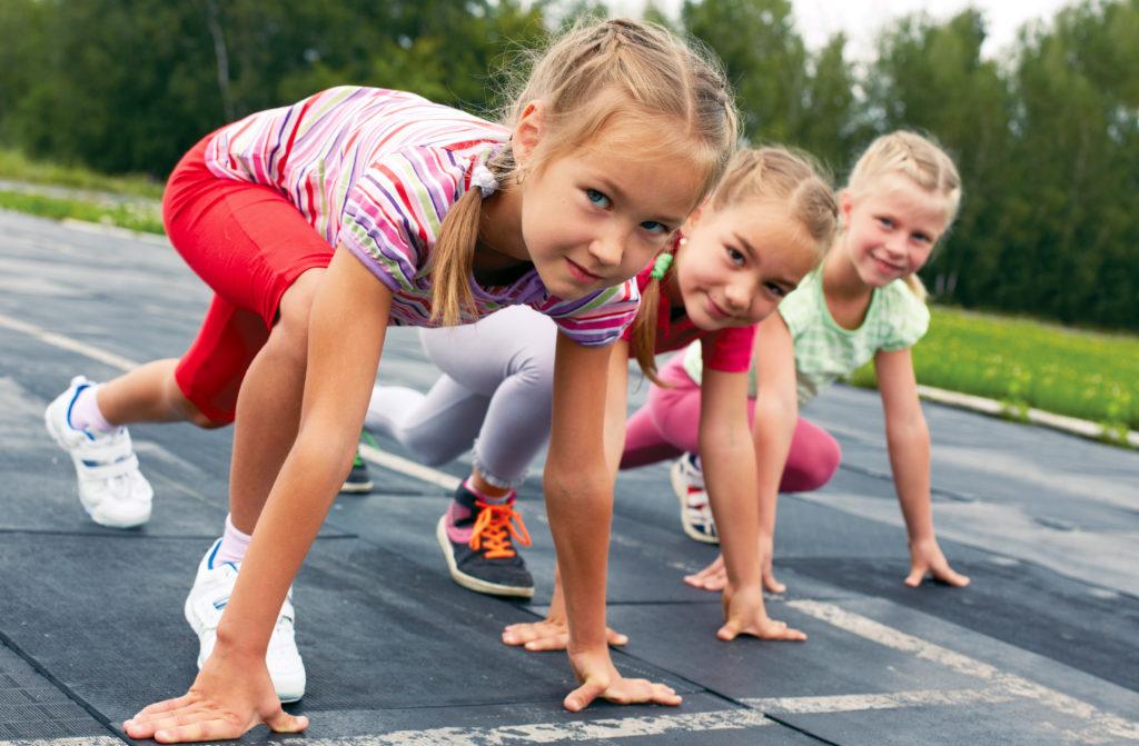 three pre-teen girls starting to run on track