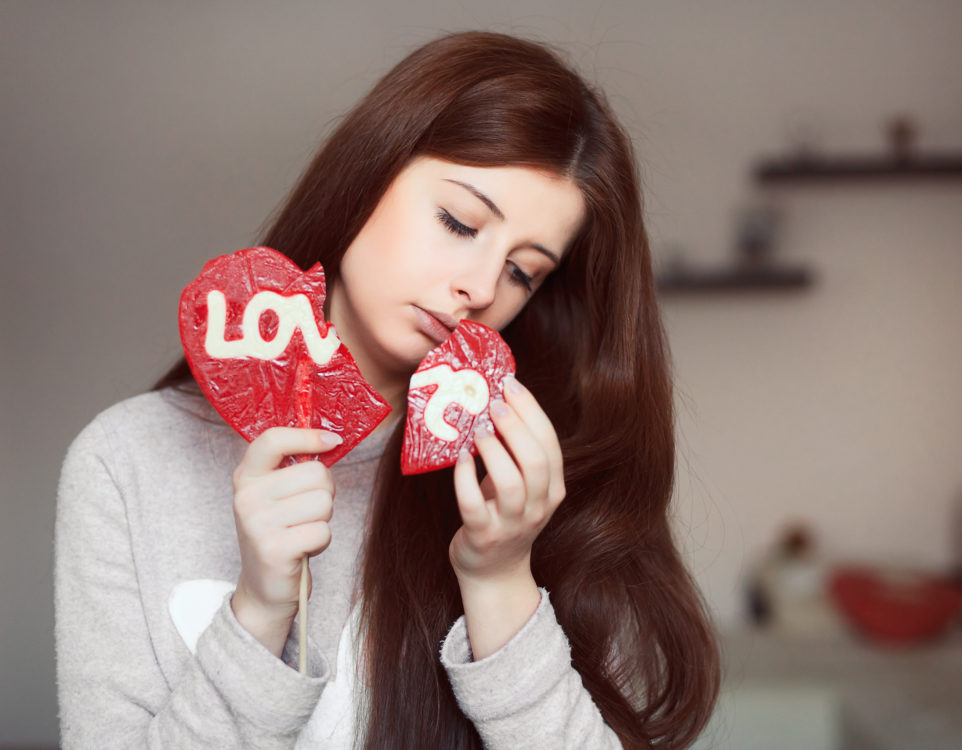 Young woman portrait with broken heart lollipop in arms