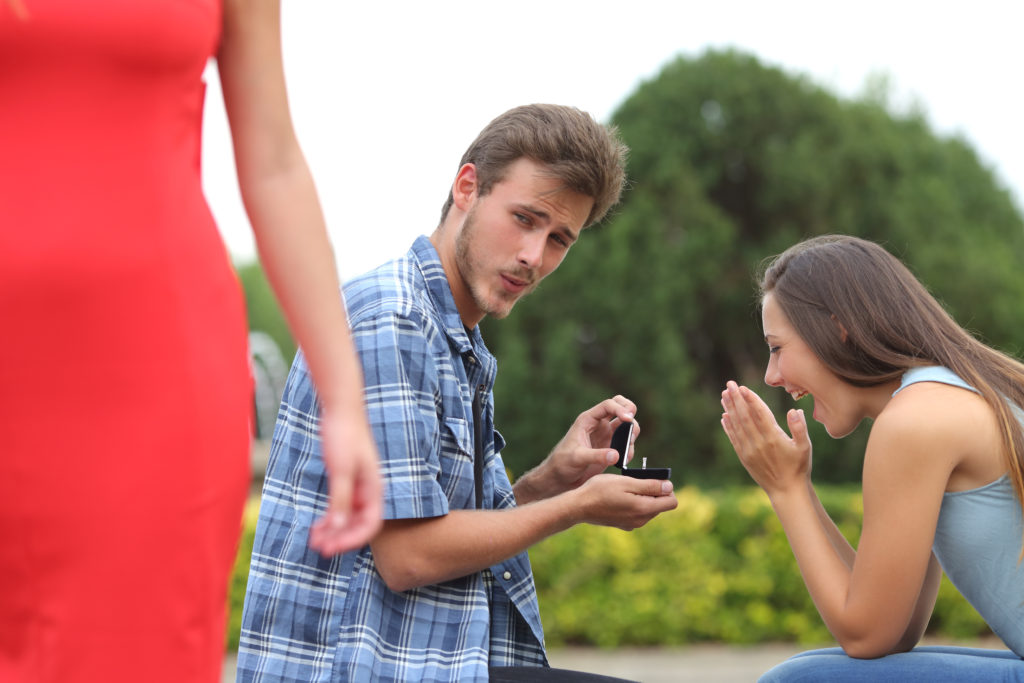 Cheater man cheating during a marriage proposal with his innocent girlfriend