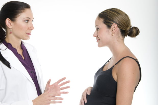 dark haired pregnant woman consults with female doctor