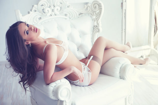Beautiful alluring young woman in sexy white lingerie sitting on the floor near luxury armchair