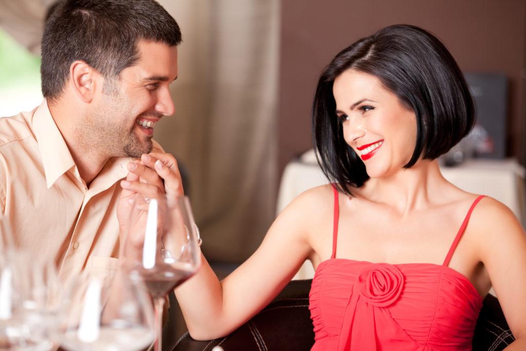 happy couple flirting at restaurant table