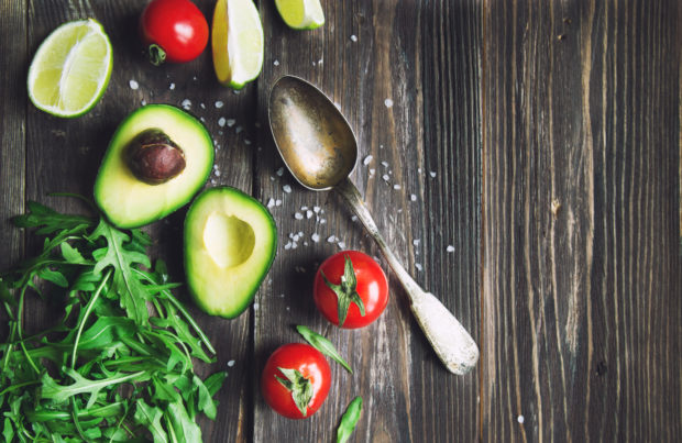 Fresh avocado, lime, tomatoes and arugula with old spoon on rustic wooden background. Top view.