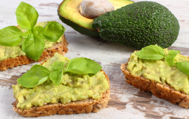 Freshly prepared sandwiches with paste of avocado, rye bread, basil, concept of healthy food, nutrition and omega fatty acids
