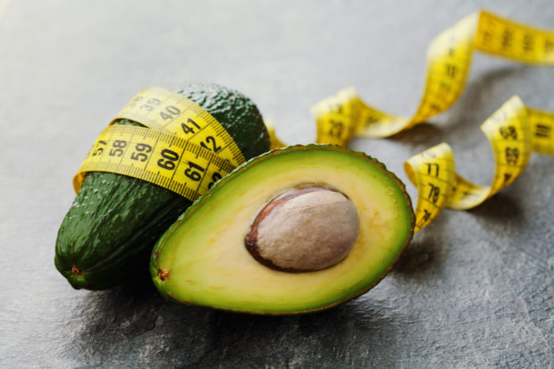 Avocado half and whole with tape measure on black background, diet concept