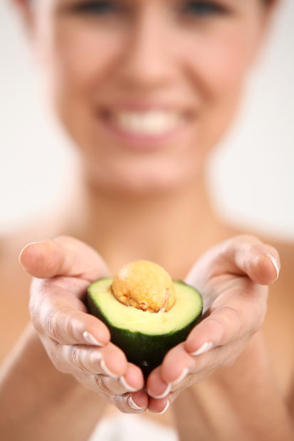 Beautiful and attractive woman portrait with fresh avocado in hand