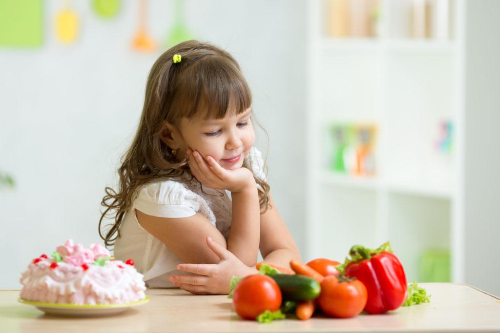 child girl choosing between healthy vegetables and tasty sweets