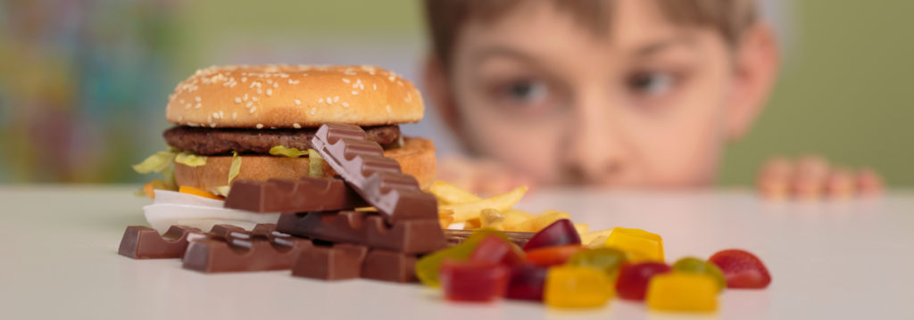 Panorama of boy and unhealthy junk food