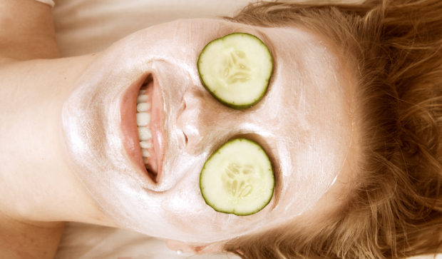 Woman with facial mask and cucumbers