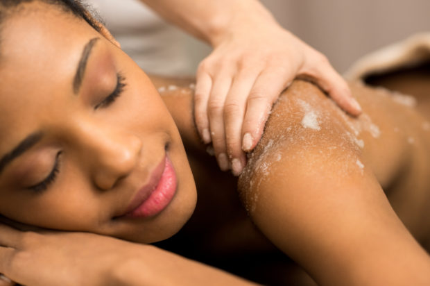 Spa therapist applying massage salt on young woman back at spa