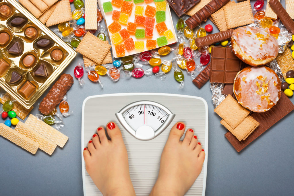 Unhealthy diet - overweight. Feet on bathroom scale and chocolate, jelly cubes, candies, chocolate bars, cookies, donuts