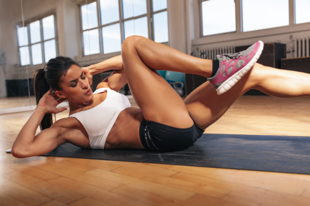 Young fit woman exercising in a gym lying on mat doing leg raising and twisting exercises. Young attractive woman doing abs workout. Fitness woman doing a sit up.