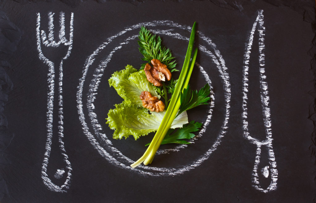 Healthy food concept. Fresh organic green salad on a chalk painted plate.