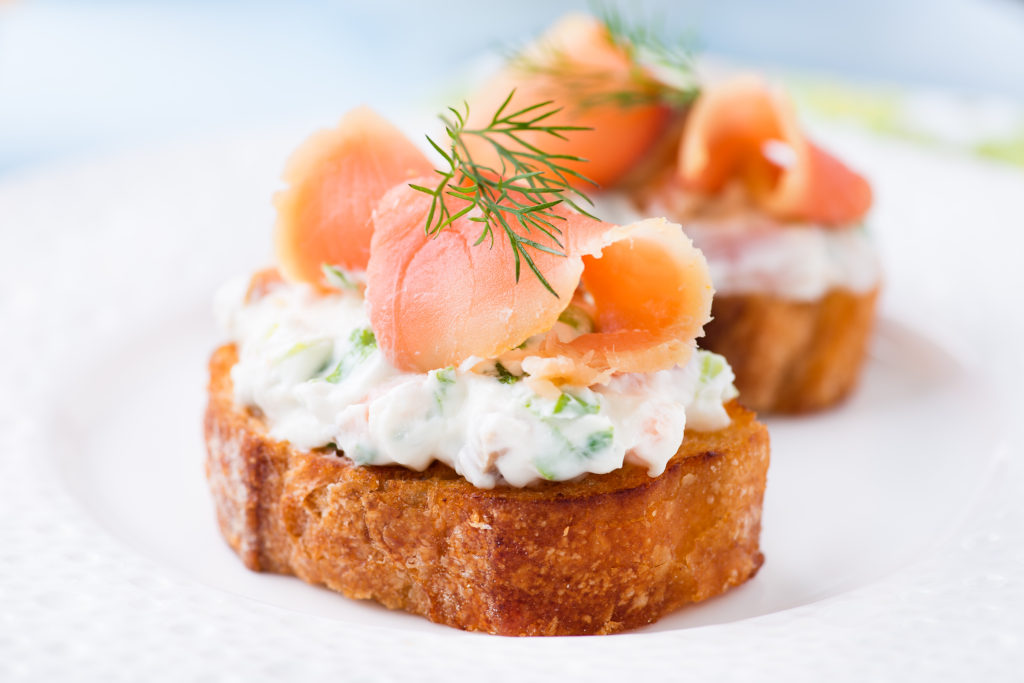 Canape with smoked salmon and cream cheese on plate, selective focus, low angle view