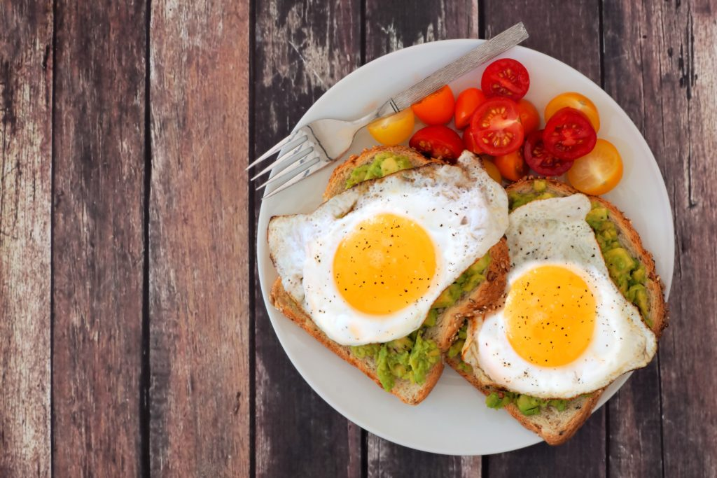 Healthy avocado, egg open sandwiches on a plate with colorful tomatoes against a rustic wood background