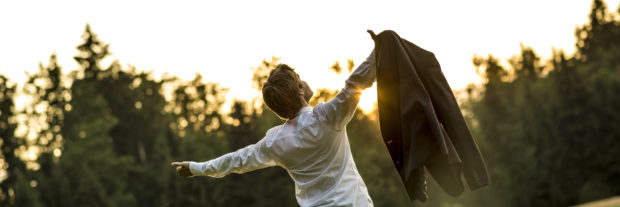 Young businessman holding his jacket with arms spread widely as he celebrates success and accomplishment standing outside in beautiful nature as the sun is setting.