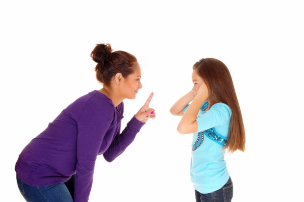 A mother is disciplining her young daughter and the girl holding her ears closed, isolated for white background.