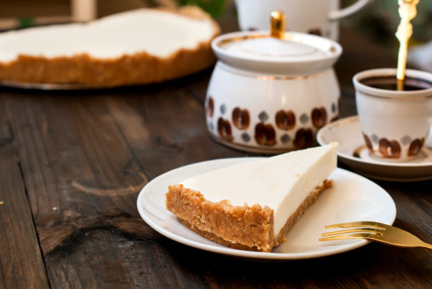 slice of cheesecake and a cup of black coffee for breakfast, a wooden background, top view