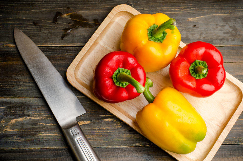 Red and yellow bell pepper or sweet pepper ready for cooking on wooden background