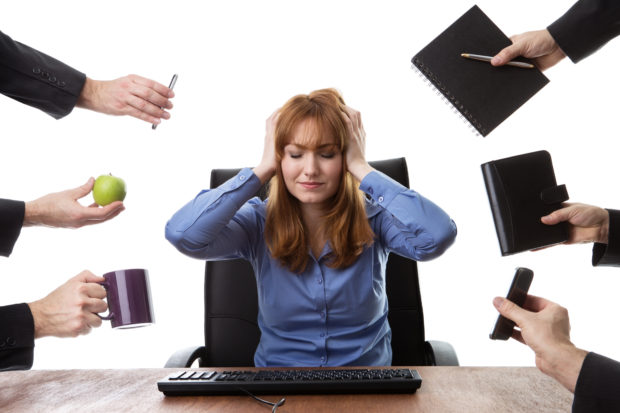 overwhelmed business woman sitting at her desk surrounded by many male hands holding different objects
