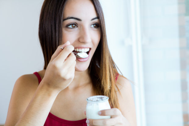 Portrait of young woman at home eating yogurt