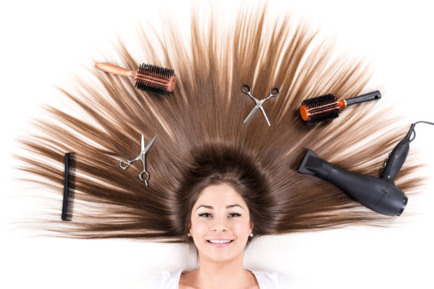 Cute young girl with Beautiful healthy shiny hair and Haircutting Equipment.