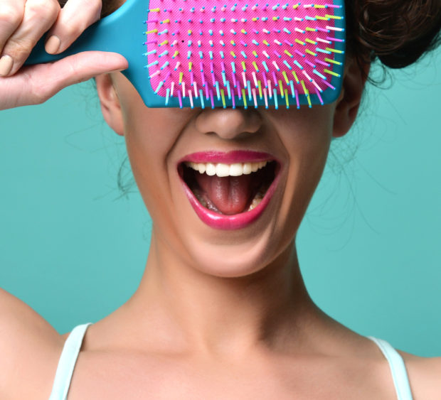 Closeup portrait of happy fashion brunette woman close eyes with colorful pink blue big hair brush on modern mint background