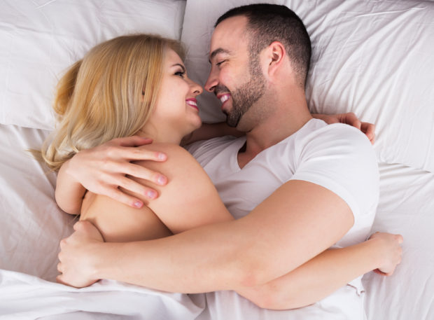 Portrait of young spouses making love in bedroom