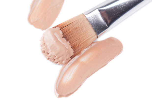 Close-up of makeup concealer pencil on white background