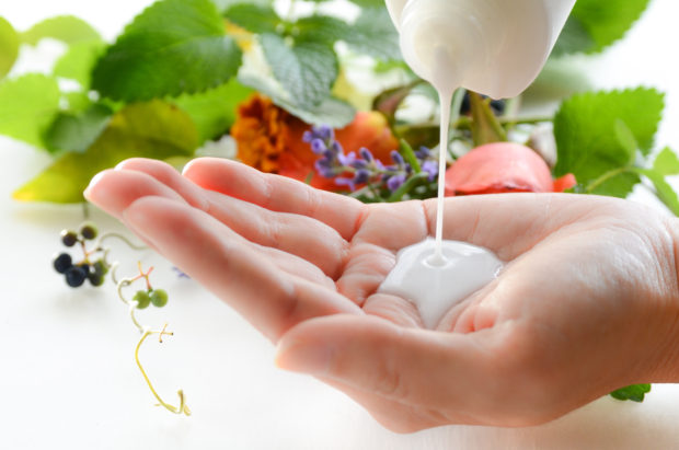 milky lotion for beauty treatment with fresh herbs in background