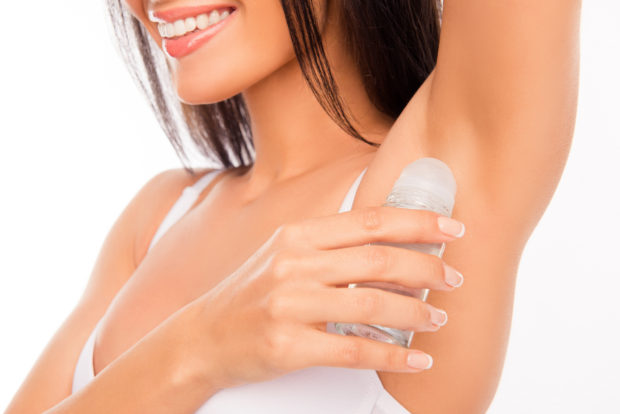 Close up photo of smiling young girl using deodorant.