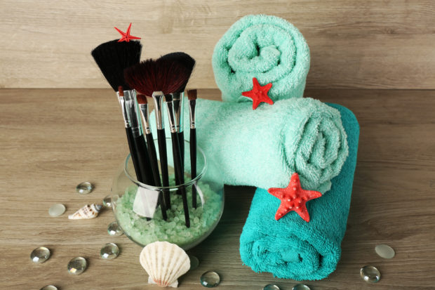 Beautiful composition with towels and brushes on wooden background