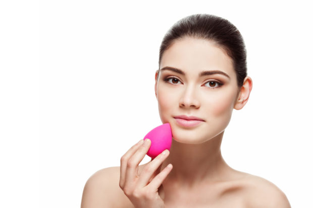 Beautiful young woman applying makeup using beauty blender sponge. Isolated over white background