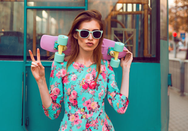 Beautiful hipster fashion young woman model posing with a pink skateboard on city background