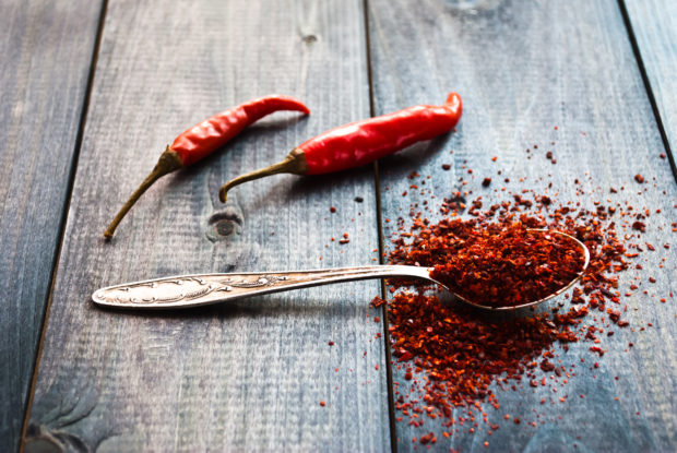 Full tea spoon of ground chili pepper and whole raw red chilies on wooden background