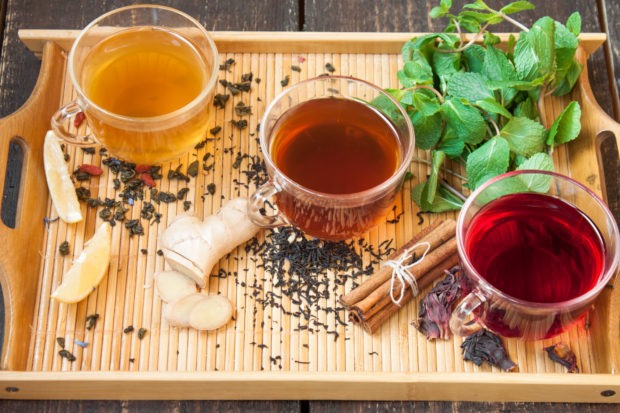 Three cups of tea with lemon, ginger, cinnamon and mint