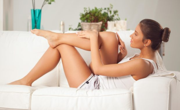 Beautiful woman sitting on a sofa and applying moisturizer.