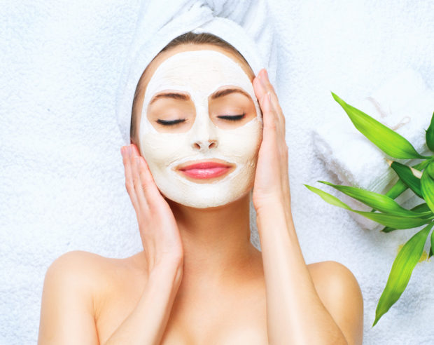 Spa woman applying facial cleansing mask
