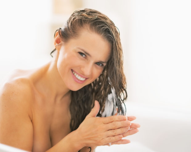 Happy young woman applying hair conditioner