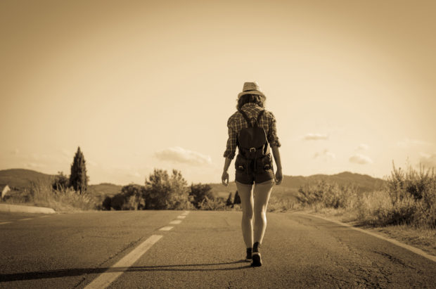 traveler is walking in the road during her trip - people, lifestyle and holidays concept